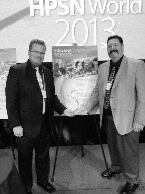 Dave Oleson and Brian Hendrickson hold award received at 2013 HPSN world conference